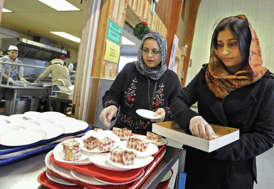 Tahira Khan of Glenville, left, and Humaira Asim of Colonie put cheesecake squares on plates at the Salvation Army soup kitchen in Schenectady, NY, on December 24, 2010. Members of the local Ahmadiyya Muslim community helped the Salvation Army staff during the busy preparation of the holiday meal on Christmas Eve.  (Lori Van Buren / Times Union) Photo: Lori Van Buren
