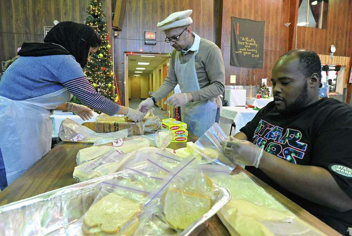 From left, Afsheen and Khalid Khan, both visiting from Dubai, and Thomas Greene of Schenectady fill bags with bread and butter at the Salvation Army soup kitchen in Schenectady, NY, on December 24, 2010. Members of the local Ahmadiyya Muslim community helped the Salvation Army staff during the busy preparation of the holiday meal on Christmas Eve. (Lori Van Buren / Times Union)