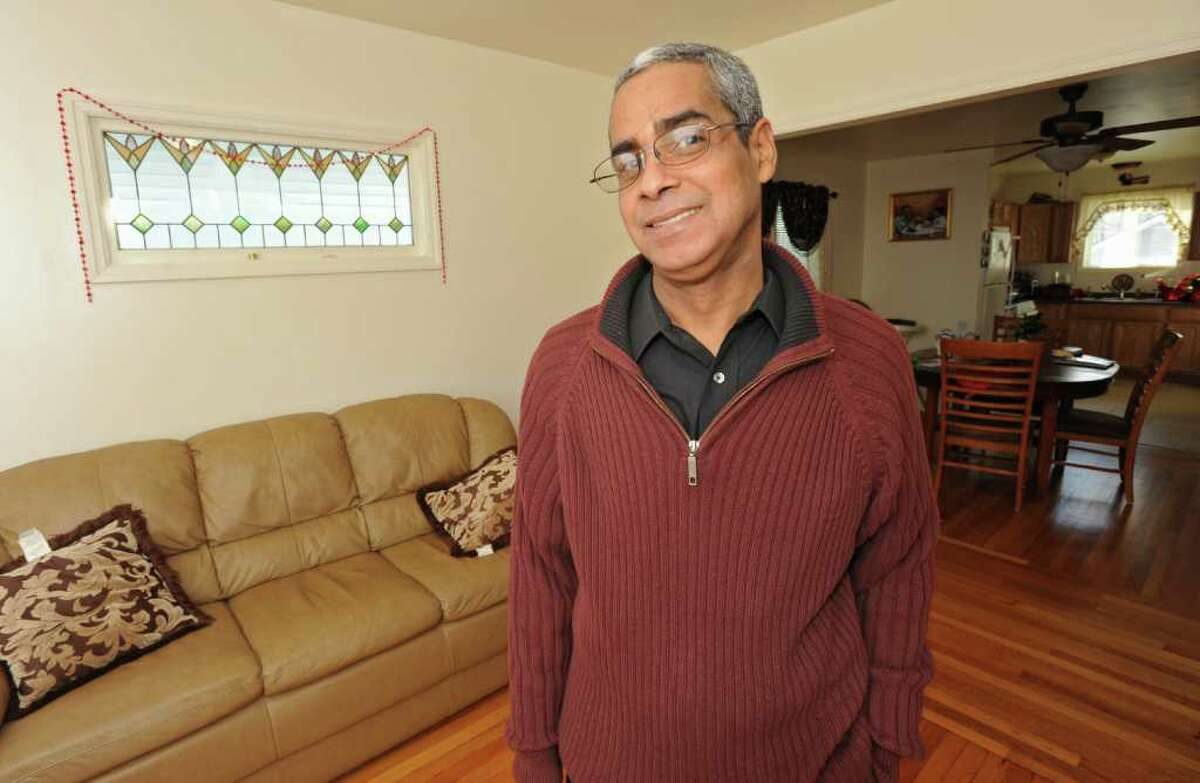 Pastor Angel Candelario appears in the living room of his home in Schenectady on December 24, 2010. The pastor is temporarily holding services at his house after a fire burned a building housing his predominantly Hispanic church . (Lori Van Buren / Times Union)