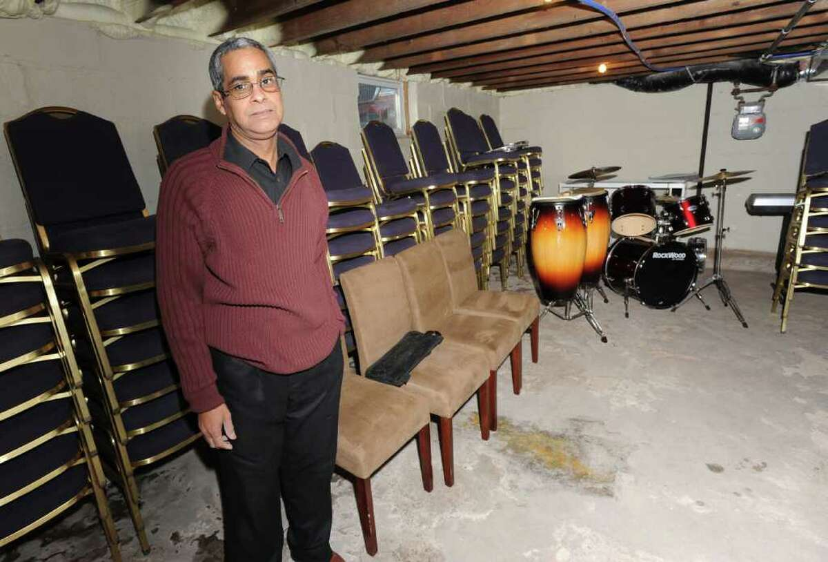Pastor Angel Candelario in the basement of his Schenectady home on December 24, 2010. Chairs and drums are stored in the basement following a fire in the building that housed his church. (Lori Van Buren / Times Union)