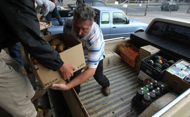 Tony Perez of Daily Bread Ministries (in truck) receives a box of potatoes that will be delivered to a church or outreach group helps feed the hungry and homeless. Photo: JOHN DAVENPORT/jdavenport@express-news.net