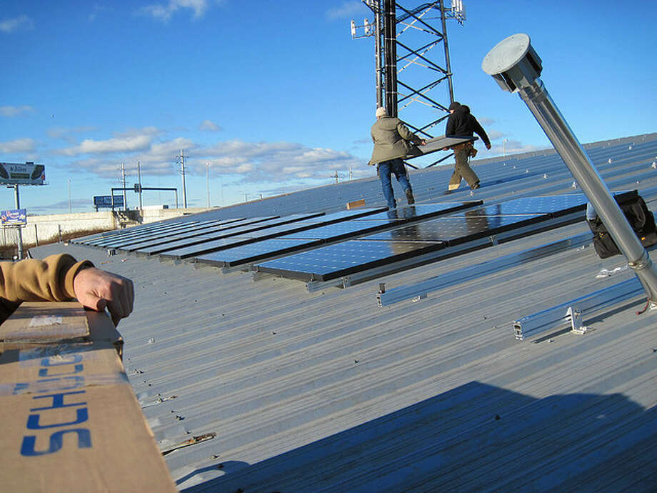 Workers from Old Greenwich-based Sound Solar Systems installing panels on a 20,000 square foot section of the Royal Flush building in Bridgeport earlier this year.  Sound Solar Systems officials say the sun-powered solar system generates up to 35 percent of the building's electricity needs. Photo: Contributed Photo / Connecticut Post Contributed