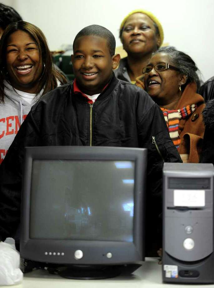 Tyjai Reddick, 12, smiles after being given a computer as a Christmas gift at the East End Community Council on Christmas Day, 2010. Reddick was a member of the Chargers city football team which traveled to Florida and won the American youth Football Championship. Photo: Lindsay Niegelberg / Connecticut Post