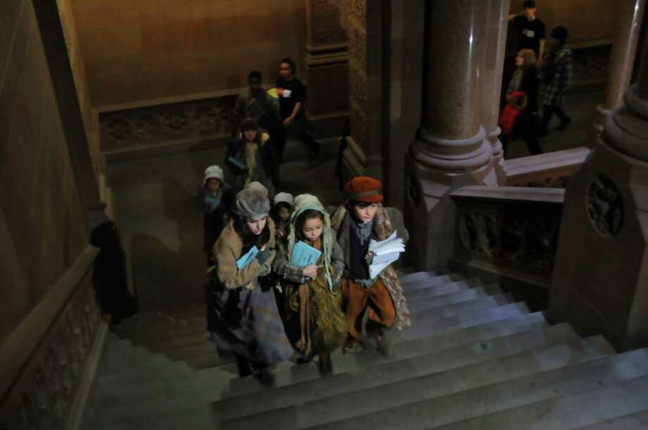 "Children in costume from the cast of the New York State Theatre Institute's (NYSTI) production ""A Christmas Carol"" head to Governor-elect Andrew Cuomo Attorney General's office on the second floor in the Capitol in Albany, NY to drop  off stacks of signed cards to ask for support for NYSTI, on Monday afternoon December 20, 2010. ( Philip Kamrass / Times Union ) Photo: Philip Kamrass / 00011488A"