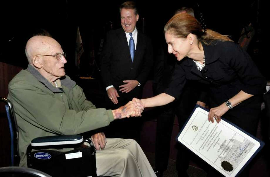 Susan Bysiewicz, Secretary of the State of Connecticut, congratulates Leonard Hurgin, 88, for his role in World War II during the Secretary of the State of Connecticut Public Service Awards ceremony at Bethel High School, Friday, Nov. 12, 2010. State Rep. David Scribner looks on. Photo: Michael Duffy / The News-Times