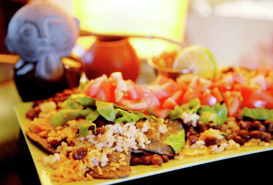 Nachos at Lil' Buddha Tea on Lark St. in Albany, NY, on Monday, Dec. 20, 2010.  The Nachos are toasted organic flax seed corn blue chips, topped with black beans and rice, melted cheddar cheese, fresh tomatoes, greens and homemade salsa. (Luanne M. Ferris / Times Union) Photo: Luanne M. Ferris