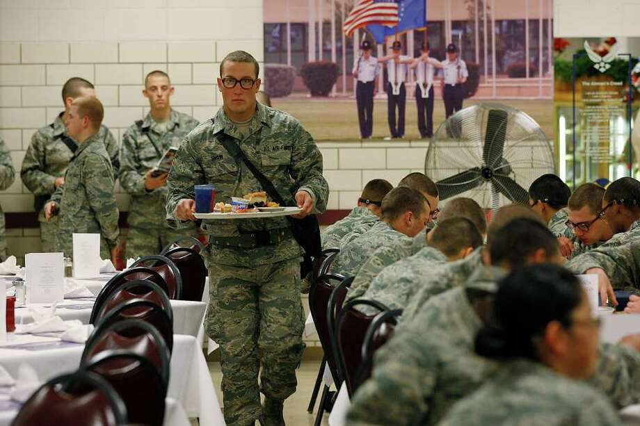 Jim Snow from Florida carries his Christmas meal to a table in the dining hall at Lackland AFB. Five thousand recruits were treated to special meals on a day when they were allowed more time to eat and the atmosphere was much more relaxed than normal. Photo: JERRY LARA, SAN ANTONIO EXPRESS-NEWS / glara@express-news.net