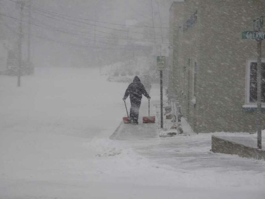 A man pushes two shovels outside New Canaan Veterinary Hospital as wind and snow whip at him during the blizzard on Dec. 26, 2010. Photo: Belinda Stasiukiewicz / New Canaan News
