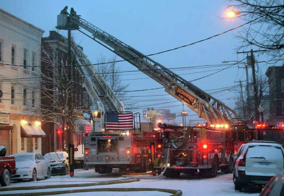 Firefighters at the scene of a fire at 1996 Main Street in Bridgeport on Sunday, December 26, 2010. Eighteen people who resided in second and third floor apartments were left homeless by the fire. Photo: Brian A. Pounds / Connecticut Post