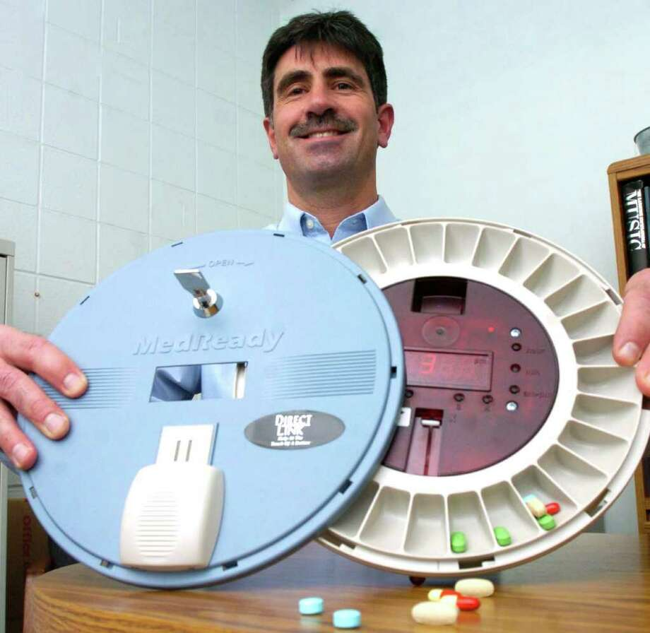 Tony Chieffo, of Home Helpers & Direct Link, is shown with a medication dispenser that has the ability to contact a help center, or family, if the patient forgets to take medication. Photo: Chris Ware / The News-Times