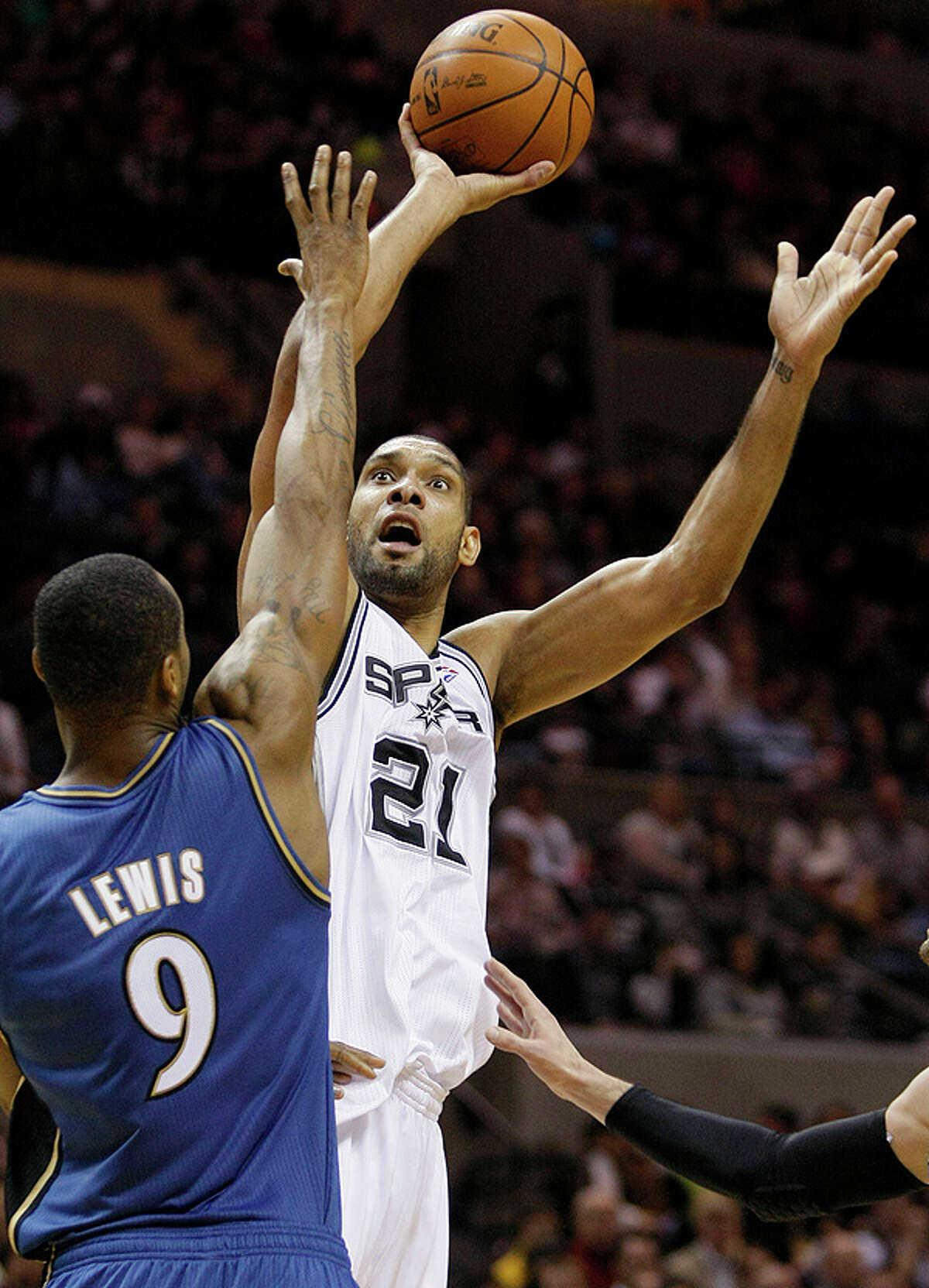 The Spurs' Tim Duncan (right) shoots over the Wizards' Rashard Lewis on Sunday at the AT&T Center.