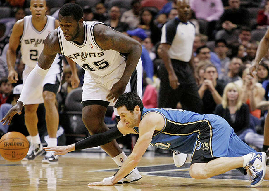 The Spurs' DeJuan Blair (left) and Wizards' Kirk Hinrich chase a loose ball  on Sunday at the AT&T Center. Photo: Darren Abate/Special To The Express-News