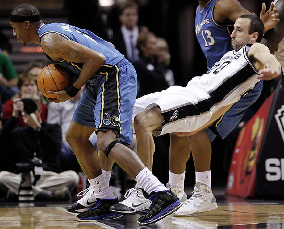 The Spurs' Manu Ginobili (right) is knocked down by the Wizards' Josh Howard  on Sunday at the AT&T Center. Photo: Darren Abate/Special To The Express-News / Copyright: Darren Abate/pressphotointl.com