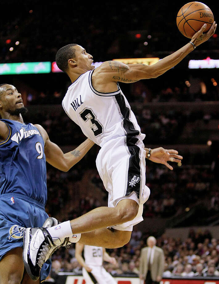 The Spurs' George Hill (right) shoots around the Wizards' Rashard Lewis on Sunday at the AT&T Center.