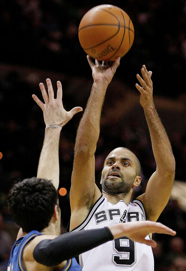The Spurs' Tony Parker (right) shoots over the Wizards' Kirk Hinrich  on Sunday at the AT&T Center. Photo: Darren Abate/Special To The Express-News