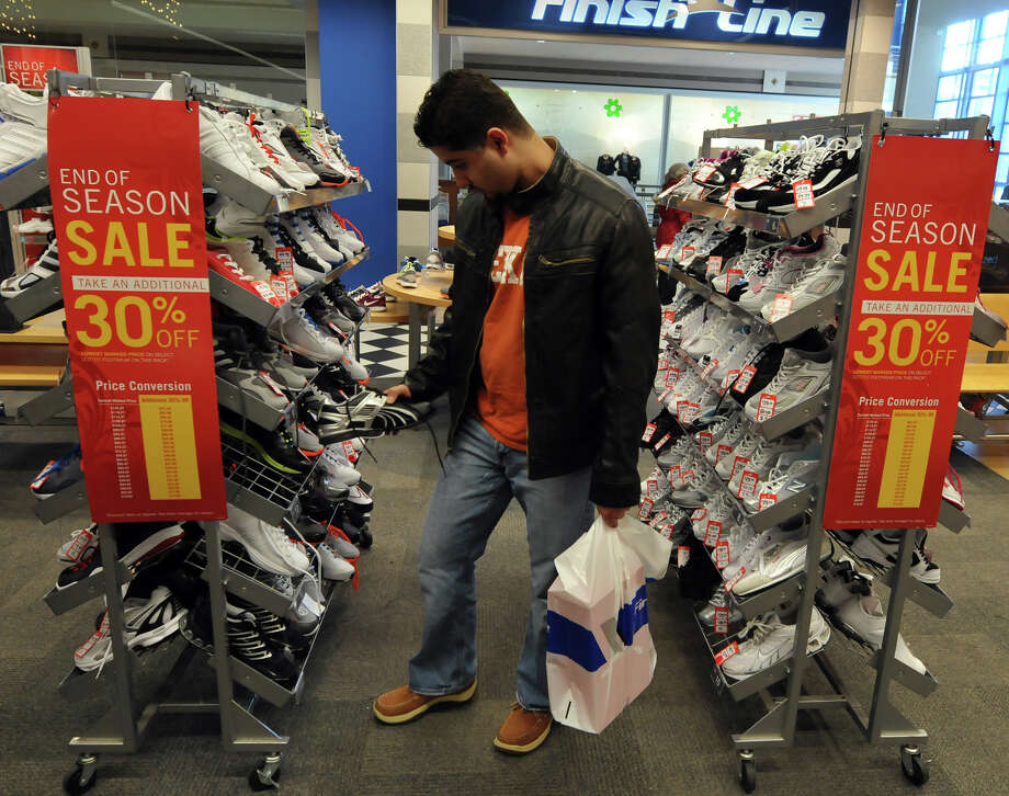 Gamo Jimenez of Houston looks at day-after-Christmas bargains at the Finish Line store in the Rivercenter mall. Photo: Robin Jerstad/Special To The Express-News / Copyright 2010 by Robin Jerstad-Jerstad Photographics LLC-www.JerstadPhoto.com