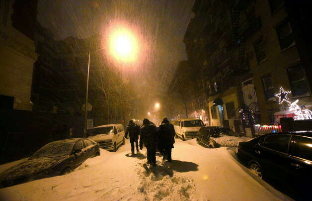 Snow blankets Manhattan's East Village early Monday morning. A winter storm pounding the East Coast  is expected to deliver a foot of snow to New York City and New England while snarling post-Christmas travel. (Mario Tama / Getty Images)