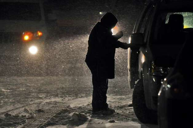 A traveler helps a passenger out of their vehicle Sunday night as they head  into the rest area at New Baltimore on the Thruway. ( Philip Kamrass / Times Union ) Photo: PHILIP KAMRASS