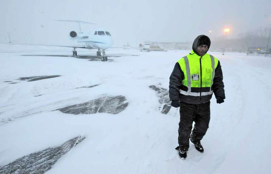 Ronald McClenon, a technician for Million Air Flight Service at  Albany International Airport, walks among several numerous private jets Monday morning that were parked overnight due to heavy snowstorm blanketing the East Coast. (Skip Dickstein / Times Union) Photo: Skip Dickstein