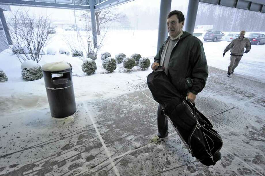 Dave Wayman heads into  Million Air Flight Service with Paul DeVoe Monday morning to catch a flight to the Caribbean Island of Nevis to play golf. Their flight was delayed by the snowstorm that hit the East Coast. (Skip Dickstein / Times Union) Photo: Skip Dickstein