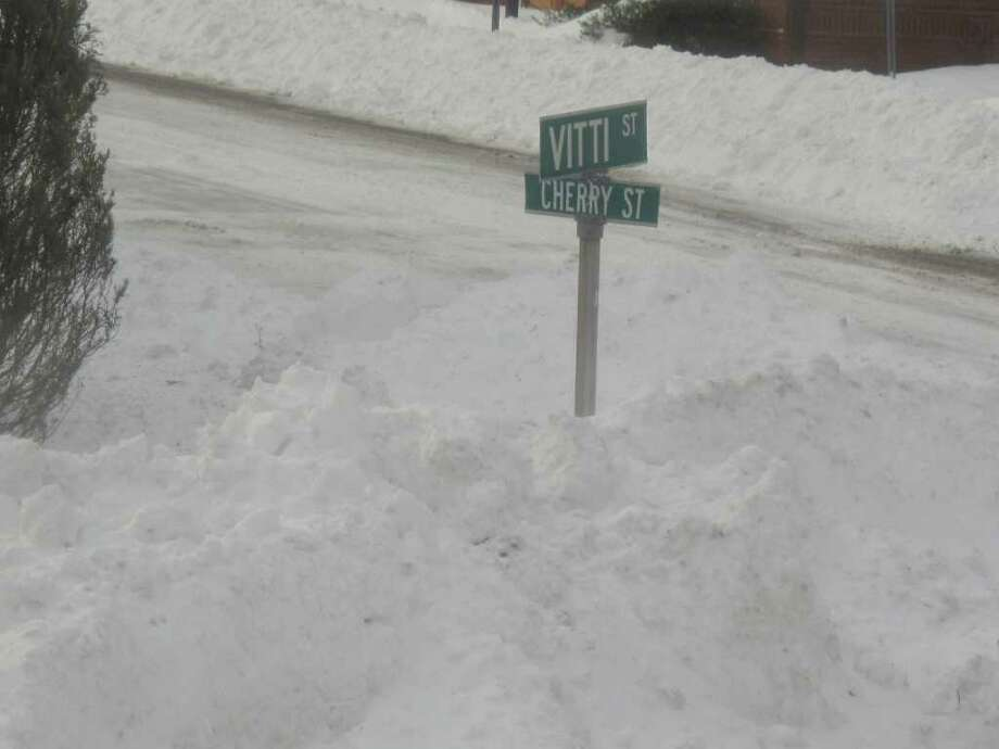 The corner of Cherry and Vitti streets in New Canaan is piled several feet high with plowed snow on Monday, Dec 27, 2010. Photo: Belinda Stasiukiewicz / New Canaan News