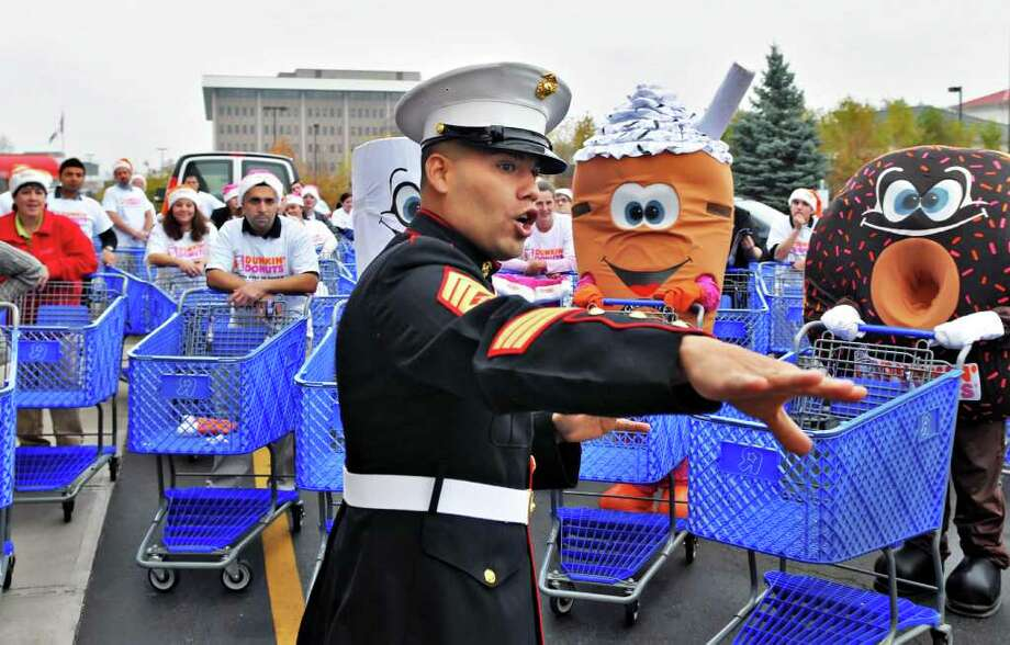 "US Marine Corps Gunnery Sergeant Albert Roman Jr. gives out marching orders to Dunkin Donuts volunteers as they begin a huge shopping spree at Toys""R""Us Us in Colonie to prepare for the Dunkin? Donuts Toys for Tots Train's annual trip throughout New York State this weekend. (John Carl D'Annibale / Times Union) Photo: John Carl D'Annibale / 00011070A"