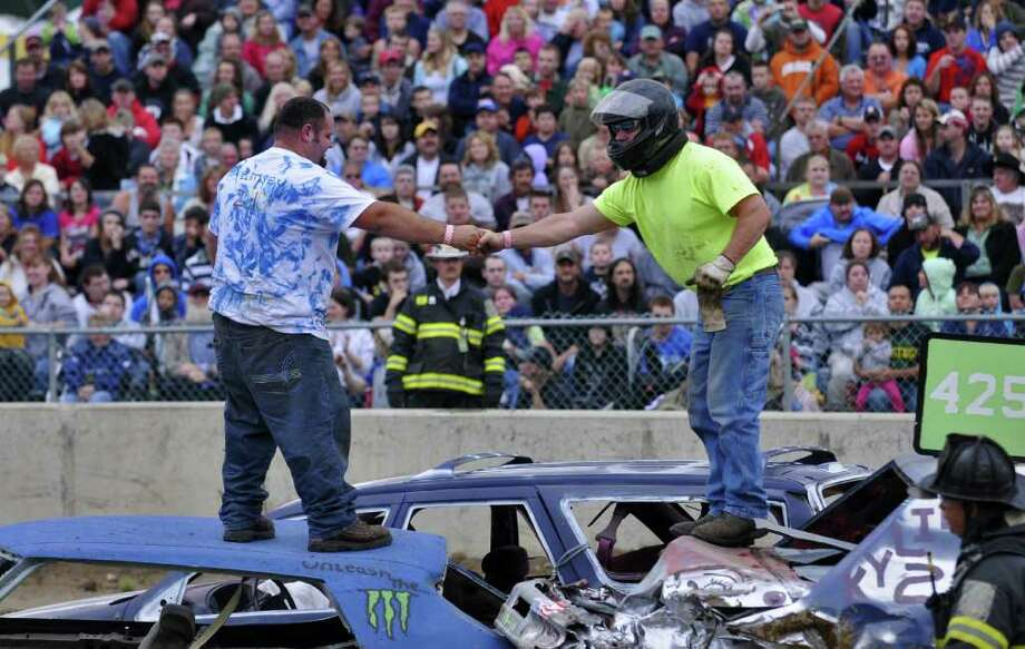 Drivers stand atop their ruined cars to shake hands after the end of the first heat of the Demolition Derby on the first night of the Washington County Fair in Greenwich, Monday August 23, 2010. (Philip Kamrass / Times Union) Photo: Philip Kamrass / 00009822A