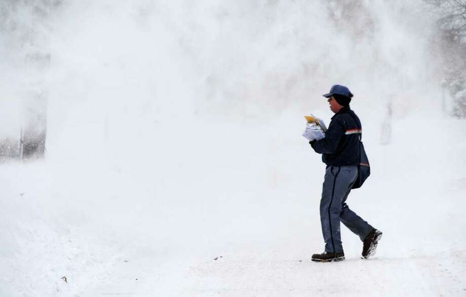Letter carrier Jim Mehan is framed by blowing snow in Chatham after a snow storm pelted the area on Monday, Dec. 27, 2010.   (Skip Dickstein / Times Union) Photo: SKIP DICKSTEIN / 2008
