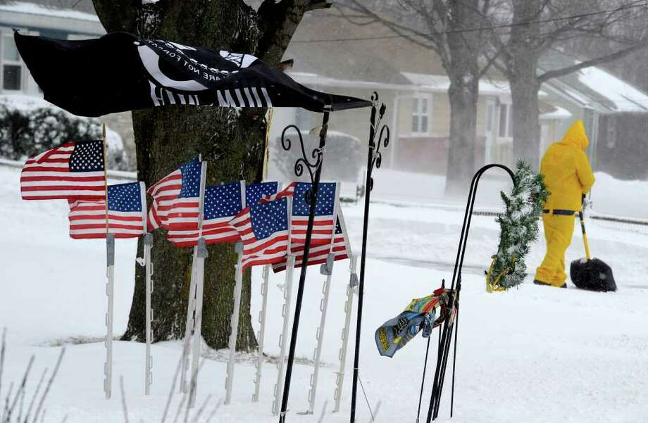 Tom Peppas shovels snow as the flags on his property are blown straight out by the high winds in East Greenbush after a snow storm pelted the area on Monday, Dec. 27, 2010.   (Skip Dickstein / Times Union) Photo: SKIP DICKSTEIN / 2008