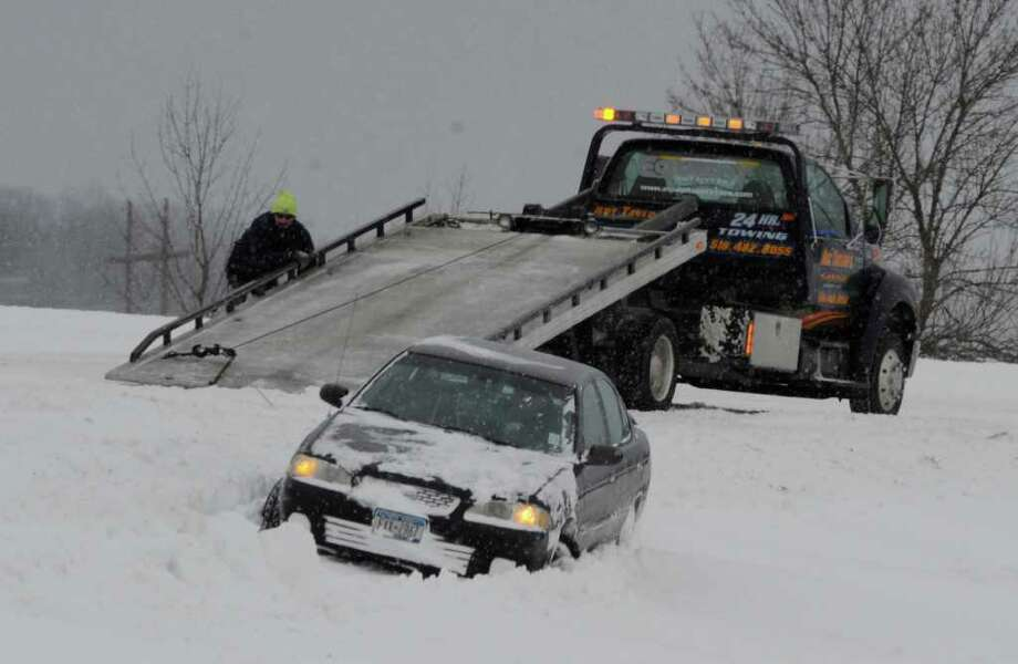 A car is winched from the median on Intestate 90 in East Greenbush after a snow storm pelted the area on Tuesday, Dec. 27, 2010.   (Skip Dickstein / Times Union) Photo: SKIP DICKSTEIN / 2008