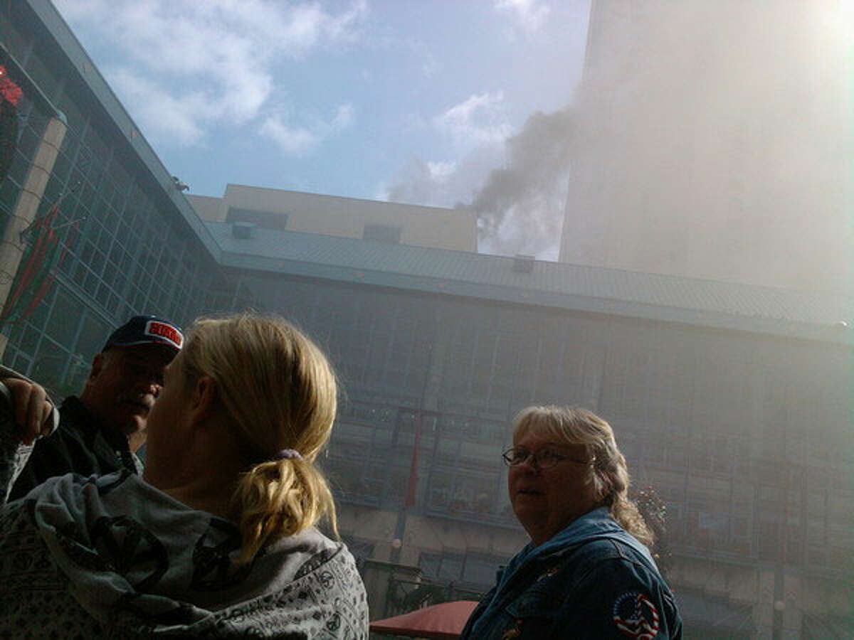 People peer at the smoke billowing from Rivercenter Mall. Numerous stores and restaurants were evacuated.