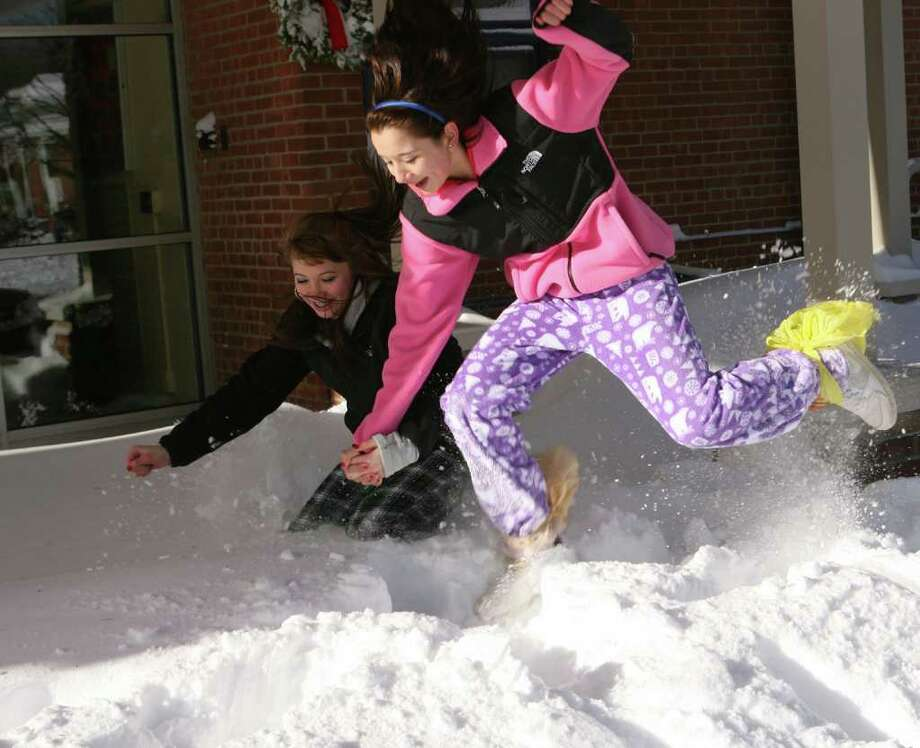 Skyler Nevins, left, and Megan Gritz, both 13 of Milford, jump in the snow with homemade snow boots at Orange Avenue School in Milford on Monday, December 27, 2010. Photo: B.K. Angeletti / Connecticut Post