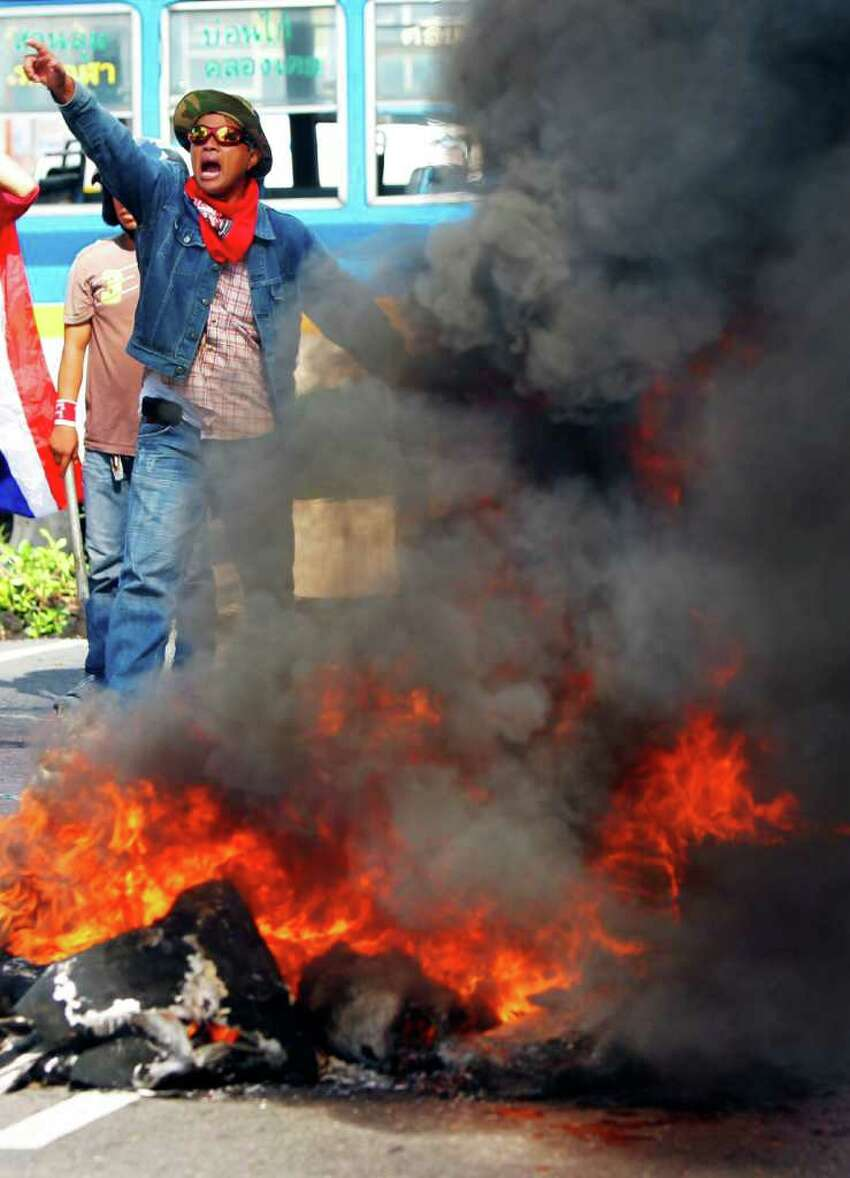 BANGKOK, THAILAND - APRIL 13: Red shirt protesters burn tyres as members of theThai military take over the streets during violent protests on April 13, 2009 in Bangkok, Thailand. Anti-government protesters clashed with the military on the streets of Thailand's capital after the government declared a state of emergency. The pro-Shinawatra demonstrators are calling for the resignation of Prime Minister Abhisit Vejjajiva and for fresh elections to be held. (Photo Paula Bronstein/Getty Images)