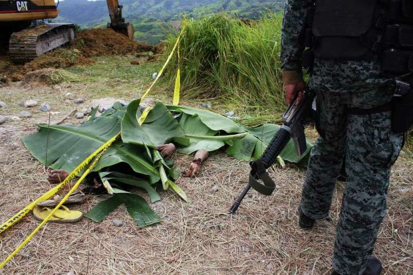 MAGUINDANAO PROVINCE, PHILIPPINES - NOVEMBER 24: The bodies of victims are recovered following the massacre of at least 46 kidnap victims on Monday in Ampatuan town, on November 24, 2009 in Maguindanao Province, Philippines. Around 100 gunmen are reported to have hijacked the party, including the wife, sister and other relatives of Buluan's Vice Mayor Esmael Mangudadatu, en route to filing election papers for candidate Mangudadatu ahead of next May's elections. Mangudadatu's wife, sister and family members, Armed Forces of the Philippines, civilians and at least 12 media personnel are thought to be amongst those killed in the attack, believed to be politically motivated. The Ampatuan clan, political rivals, are being blamed for the kidnap, mutilation, rape and murder of the victims. (Photo by Jeoffrey Maitem/Getty Images)