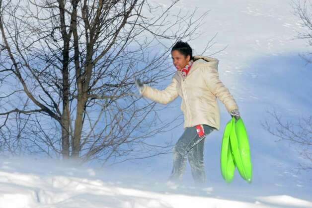 Nicole Ruiz, 12, of Albany fights with the wind as she walks up a hill while sledding in Lincoln Park in Albany, NY on December 27, 2010. (Lori Van Buren / Times Union) Photo: Lori Van Buren