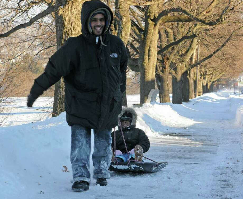Seon Hinds of Albany pulls his crying 4-year-old daughter, Kacona Hinds, after sledding in Lincoln Park in Albany, NY on December 27, 2010. The freezing wind was too much for Hacona and she wanted to go home. (Lori Van Buren / Times Union) Photo: Lori Van Buren