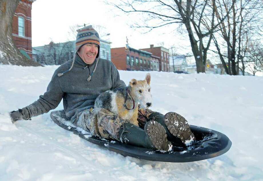 Matt Decker of Albany and his dog Scooter ride on a sled down a hill in Lincoln Park in Albany, NY on December 27, 2010. (Lori Van Buren / Times Union) Photo: Lori Van Buren