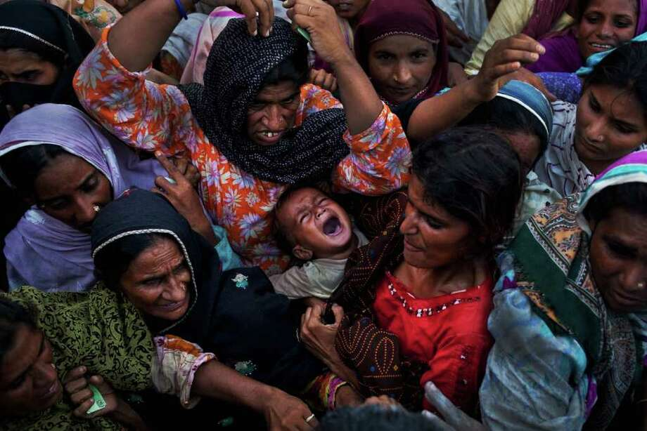 MUZAFFARGARH, PAKISTAN - AUGUST 20: A baby, held by his mother, is crushed as she and other villagers, displaced from their homes by flooding, fight for bags of flour during relief distribution on August 20, 2010 on the outskirts of Muzaffargarh in Punjab, Pakistan. The country's agricultural heartland has been devastated, with rice, corn and wheat crops destroyed by floods. Officials say as many as 20 million people have been effected during Pakistan's worst flooding in 80 years. The army and aid organizations are struggling to cope with the scope of the wide spread scale of the disaster that has killed over 1,600 people and displaced millions. The UN has described the disaster as unprecedented, with over a third of the country under water.  (Photo by Daniel Berehulak/Getty Images) Photo: Getty Images