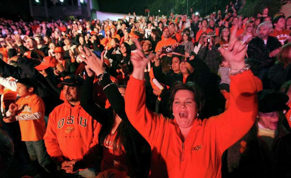 Cheryl Martinez, the mother of Oklahoma State offensive tackle Nick Martinez, cheers with other family members and fans during