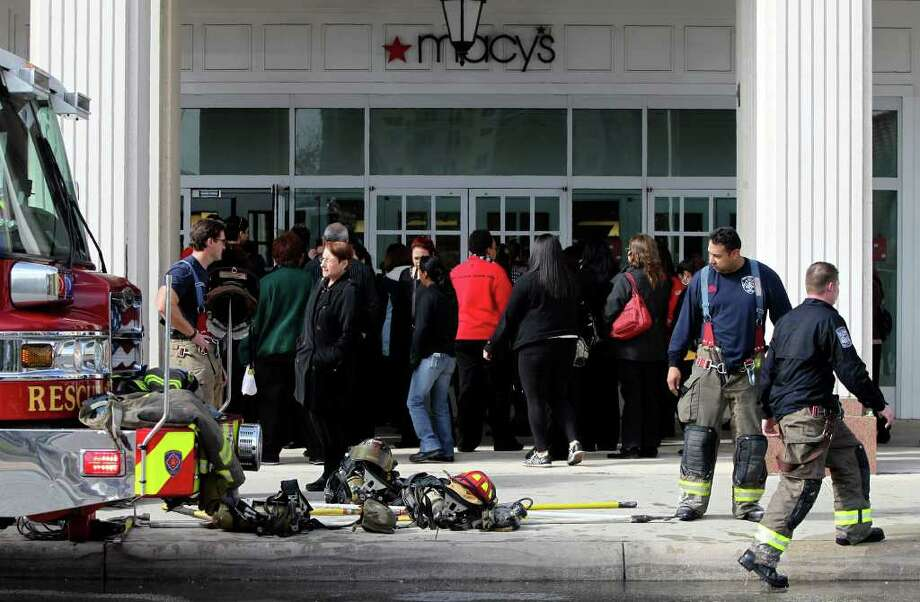 """People return to Macy's at Rivercenter Mall after the store was evacuated. """"We were only fearful of the smoke, so we evacuated part of the mall so that visitors could go outside and be safe,"""" said Priscilla Gonzaba, the mall's assistant general manager. Photo: John Davenport/Express-News / jdavenport@express-news.net"""