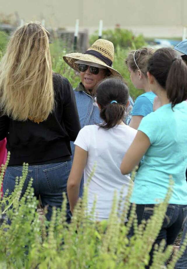 Master gardener Margaret Chavez speaks to Girl Scouts and others last month at the San Antonio Food Bank's garden, which grows organic fruits and vegetables. Photo: John Davenport/Express-News / jdavenport@express-news.net