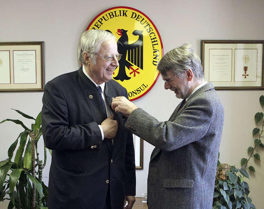 San Antonio lawyer Bernard Ben Buecker (left) receives the Commander's Cross from Germany's Consul General Roland Herrmann. Photo: John Davenport / Express-News