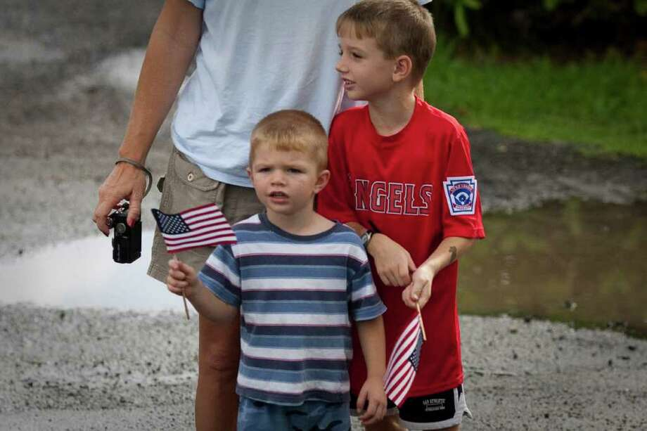 KANEOHE, HI - DECEMBER 27:  (AFP OUT) Two young boys holding American flags wave at US President Barack Obama's motorcade as it returns to Obama's vacation compound December 27, 2010 in Kaneohe, Hawaii. The Obamas visited troops at a Marine Corp. base in Hawaii during their 11-day family vacation.   (Photo by Kent Nishimura-Pool/Getty Images) Photo: Pool, Getty Images / 2010 Getty Images