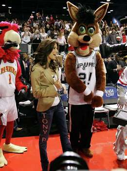 "METRO - Actress Eva Longoria gets escorted by the Spurs Coyote during introductions of the celebrity teams at the McDonald's NBA All-Star Celebrity game presented by 2K Sports at the George R. Brown Convention Center in Houston on Friday, Feb. 17, 2006. Longoria took on the role of a coach for the ""H-Town"" team that included celebrities such as hip hop artist Nelly. Longoria sported denim jeans with the words, ""Tony P"", that likely showed her support for boyfriend and Spurs guard Tony Parker who will be playing as an All-Star for the first time in his NBA career. Photo: KIN MAN HUI, SAN ANTONIO EXPRESS-NEWS / SAN ANTONIO EXPRESS-NEWS"
