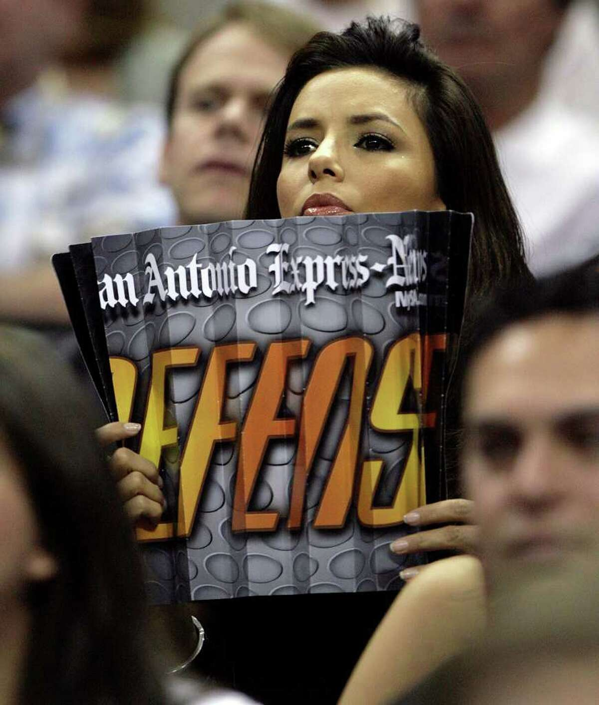 SPORTS ----- Eva Longoria holds an Express-News give-away item Saturday night May 12, 2007 at the AT&T Center in San Antonio during the Spurs' third game of their best-of-seven, second-round playoff series against the Suns.