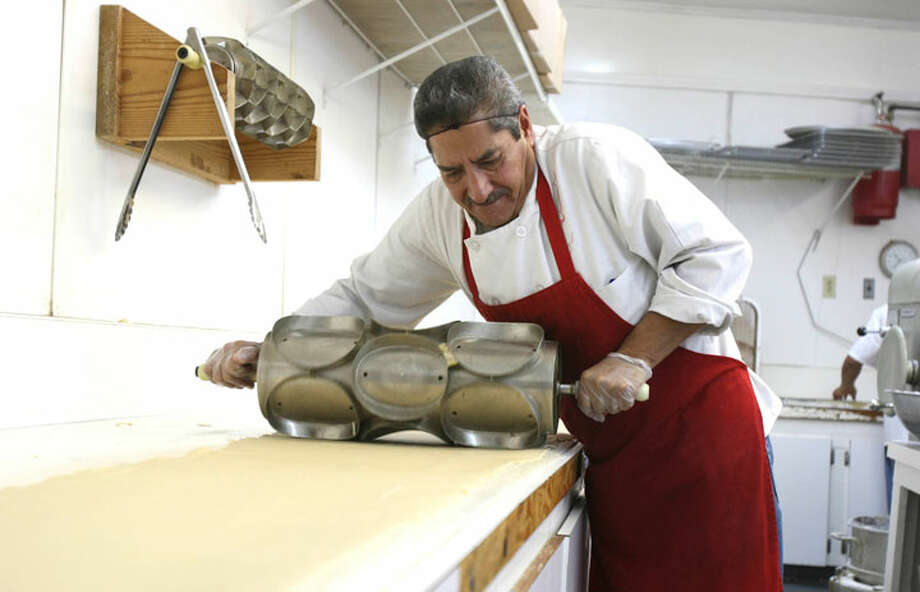 Rafael Chapa cuts the dough into round pieces before they head for the fryer at the The Original HemisFair Buñuelo company. The company has been making the sweet treats since 1968. HELEN L. MONTOYA/hmontoya@express-news.net