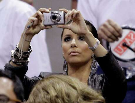 Actress Eva Longoria takes photos during Game 4 of a first-round NBA basketball playoff series between the San Antonio Spurs and the Dallas Mavericks, Sunday, April 25, 2010, in San Antonio. Photo: AP