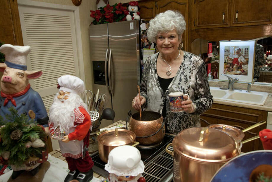 Lilo Strait serves mulled wine from a German copper pot in her kitchen, decorated in traditional German Christmas style.PHOTO BY J. MICHAEL SHORT/SPECIAL TO THE EXPRESS-NEWS