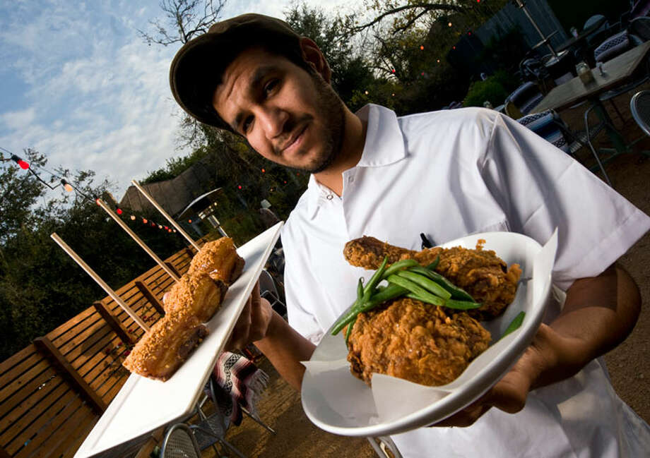 "The Monterey's chef Albert Vasquez with pork belly skewers coated in ground, smoked almonds (left) and fried chicken. He calls his fare ""glorified bar food.