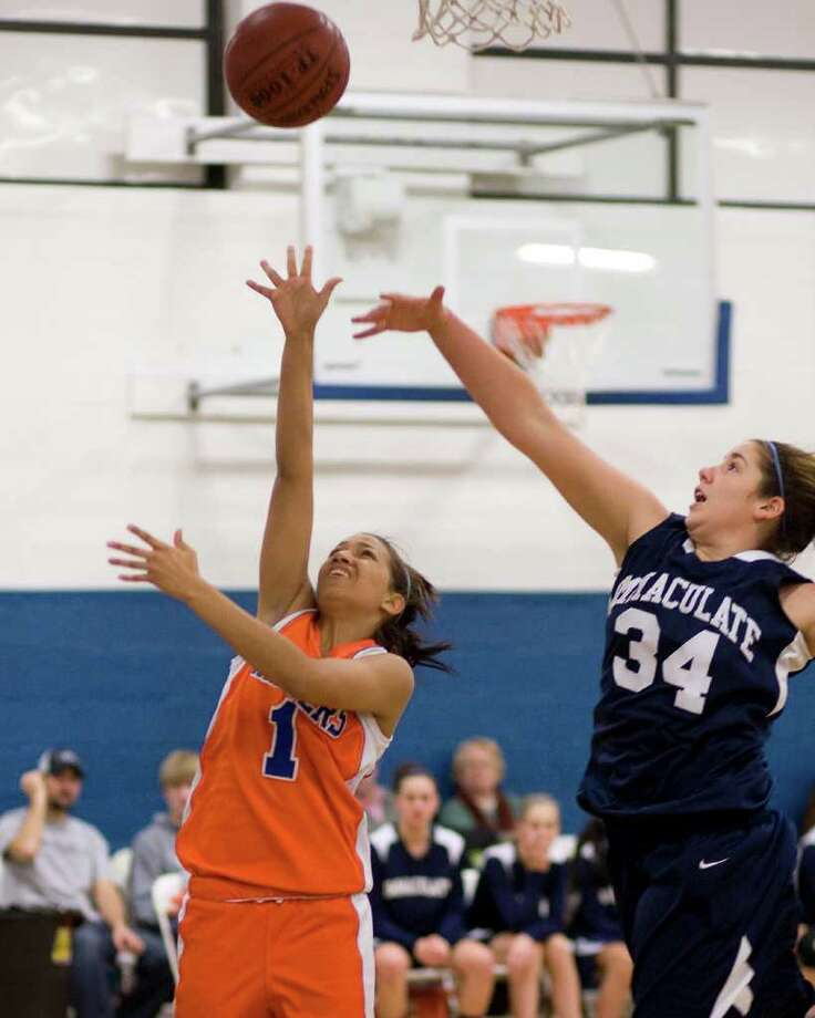 Danbury's Rabia Rawji (1) puts up a shot over Immaculate's Meghan Loya during the opening round of The News-Times Holiday Festival Tuesday night at the Danbury War Memorial. Photo: Barry Horn / The News-Times Freelance